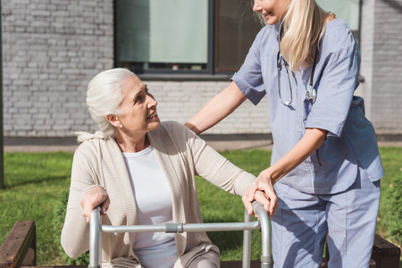 cropped shot of nurse and senior patient with walker smiling each other outside nursing home