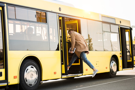 Photo pour full length view of young man holding digital tablet and entering bus - image libre de droit