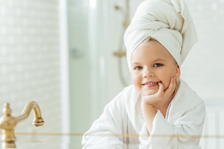 Photo pour adorable little girl in bathrobe and towel on head smiling at camera in bathroom - image libre de droit