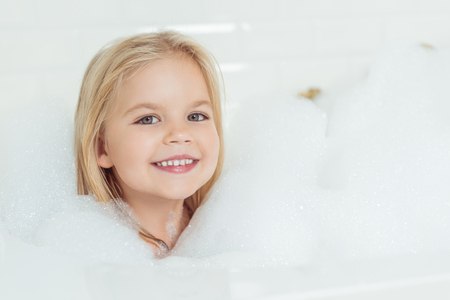 Photo pour beautiful little girl smiling at camera while sitting in bathtub with foam  - image libre de droit