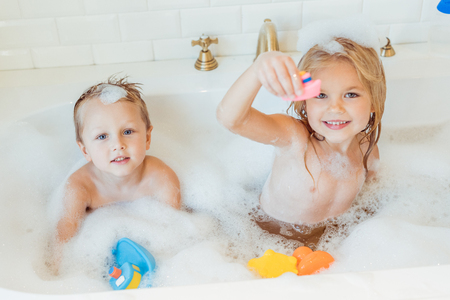 Photo pour cute little brother and sister playing with toys and smiling at camera in bathtub  - image libre de droit