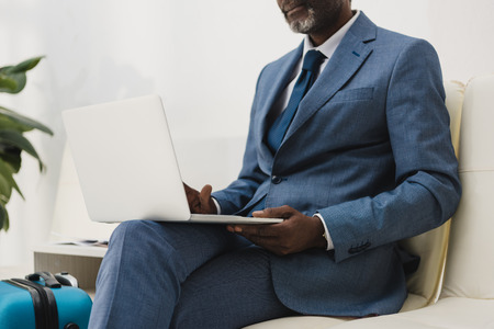 Foto de Cropped image of middle aged African american businessman working with a laptop while sitting at the airport - Imagen libre de derechos
