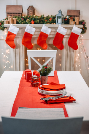 Foto de christmas table with tableware ready for serving in front of decorated fireplace - Imagen libre de derechos