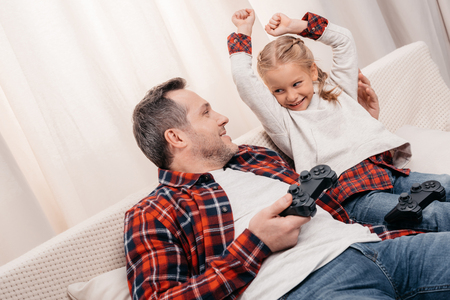 father and daughter playing with joysticks and smiling each other at home