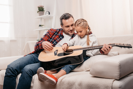 smiling father teaching cute little daughter playing acoustic guitar の写真素材