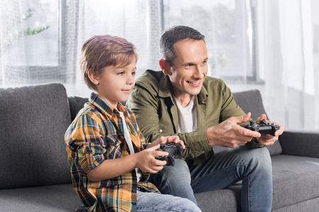 happy excited father and son playing console with gamepads while sitting on couch