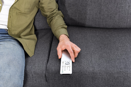 cropped shot of man with tv remote sitting on couch