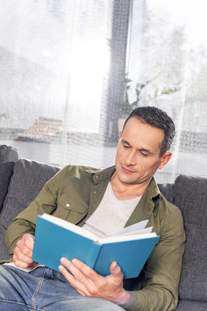handsome adult man reading book while sitting on couch