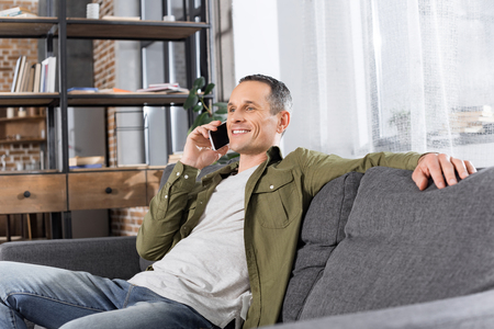 handsome man talking by phone while sitting on couch