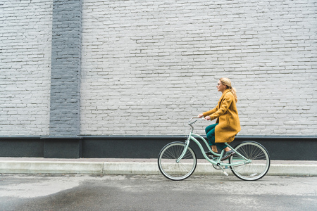 Foto de fashionable woman in yellow coat riding bicycle with grey wall on background - Imagen libre de derechos