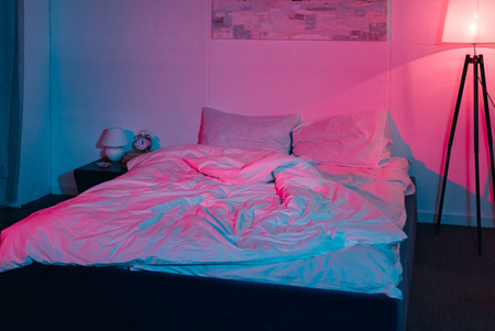 Photo pour modern empty bedroom at night with red and blue light - image libre de droit