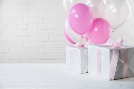 Foto de Presents on table with white and pink balloons on white brick wall background - Imagen libre de derechos