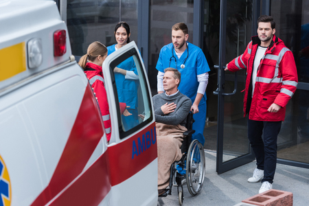 doctors helping man on wheelchair get to ambulance