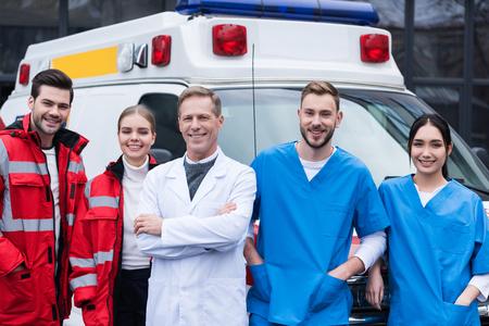 Photo pour happy ambulance doctors working team standing in front of car - image libre de droit