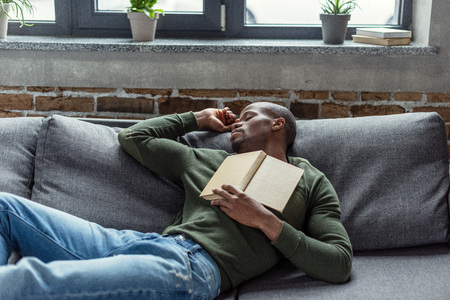 portrait of young african american man with book sleeping on sofa at home |  Stock Images Page | Everypixel
