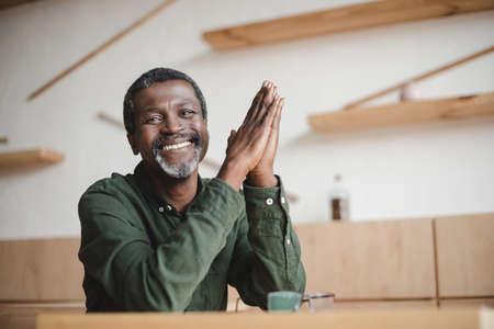 Photo pour smiling mature african american man sitting in cafe - image libre de droit
