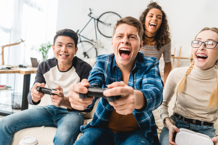 laughing multicultural teens playing video game