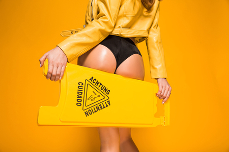 Foto de cropped image of sexy woman holding wet floor sign on orange - Imagen libre de derechos
