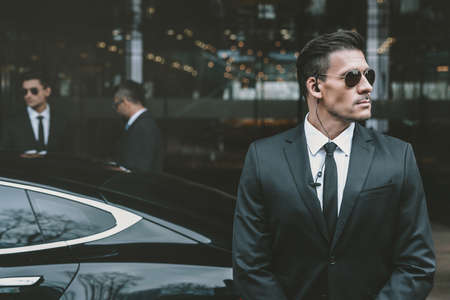 Photo pour bodyguard standing at businessman car and reviewing territory - image libre de droit