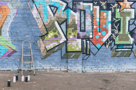 cans with spray paint and ladder near colorful graffiti on wall of building in city
