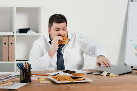 Photo pour overweight businessman eating hamburger and using laptop in office - image libre de droit