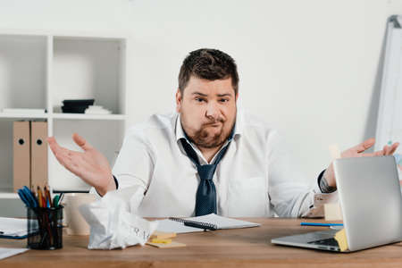 Foto de confused overweight businessman sitting at workspace with documents and laptop - Imagen libre de derechos