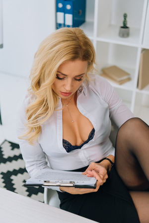 sexy woman with decollete reading working contract