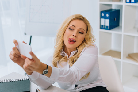 Photo pour sexy businesswoman taking selfie at working place with smartphone and sticking tongue out - image libre de droit