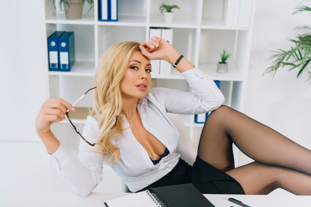 tired sexy woman sitting in chair, holding glasses and looking at camera