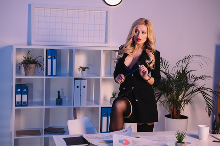Photo pour seductive woman putting leg on chair and holding pencil - image libre de droit