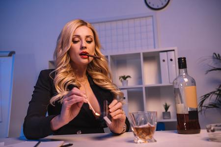 Photo pour seductive woman lighting cigar with match - image libre de droit