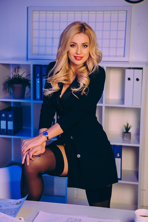 Photo pour smiling sexy woman putting leg on chair in office and looking at camera - image libre de droit