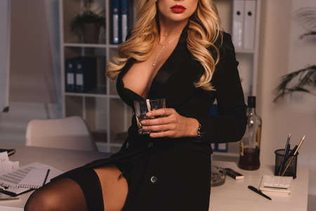 Foto de cropped image of seductive woman holding glass of whiskey in office at evening - Imagen libre de derechos