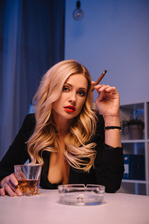 Photo pour seductive woman sitting with cigar and glass of whiskey in office and looking at camera - image libre de droit