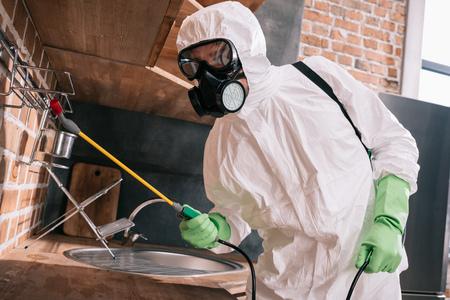 Photo pour pest control worker spraying pesticides on metal shelves in kitchen - image libre de droit