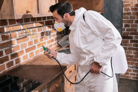 Photo pour side view of pest control worker spraying pesticides under shelves in kitchen - image libre de droit