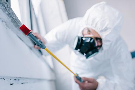 Photo pour pest control worker spraying pesticides under windowsill at home - image libre de droit