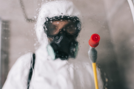 Photo pour pest control worker standing in respirator in bathroom with sprayer - image libre de droit