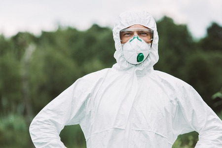 Photo for selective focus of smiling male scientist in protective mask and suit looking at camera outdoors - Royalty Free Image
