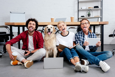 Foto de happy young business colleagues and dog sitting on floor with tongues out in office - Imagen libre de derechos