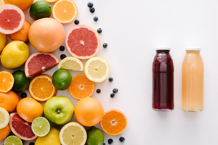 Photo pour top view of citrus fruits with blueberries and bottle of fresh juice on white surface - image libre de droit