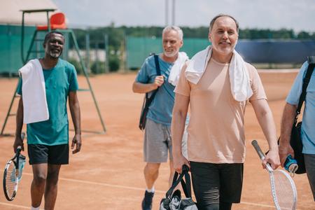 Foto de selective focus of multiracial elderly friends with tennis equipment walking on court - Imagen libre de derechos