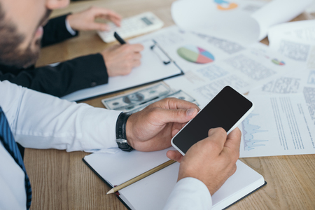 cropped image of financier using smartphone in office