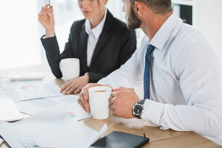 cropped image of financiers working with documents during coffee break in office