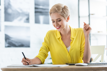 Photo for smiling female freelancer writing in textbook at table with graphic tablet and computer at home office - Royalty Free Image