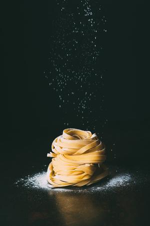 Foto de closeup shot of flour falling on tagliatelle pasta on black background - Imagen libre de derechos