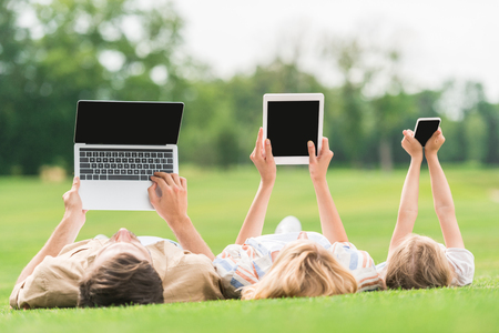 Photo pour family lying on grass and using digital devices with blank screens - image libre de droit