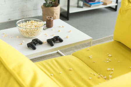 glass bowl with popcorn and joysticks on table, yellow sofa in living room