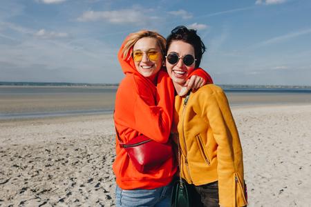 happy female friends hugging on sandy beach, Saint michaels mount, Normandy, France