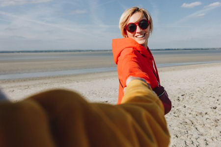 friends holding hands sandy beach, Saint michaels mount, Normandy, France
